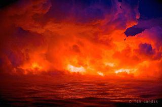multiple streams of lava plunge into a rough sea