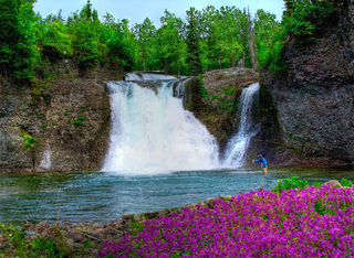 waterfall with fly fisherman