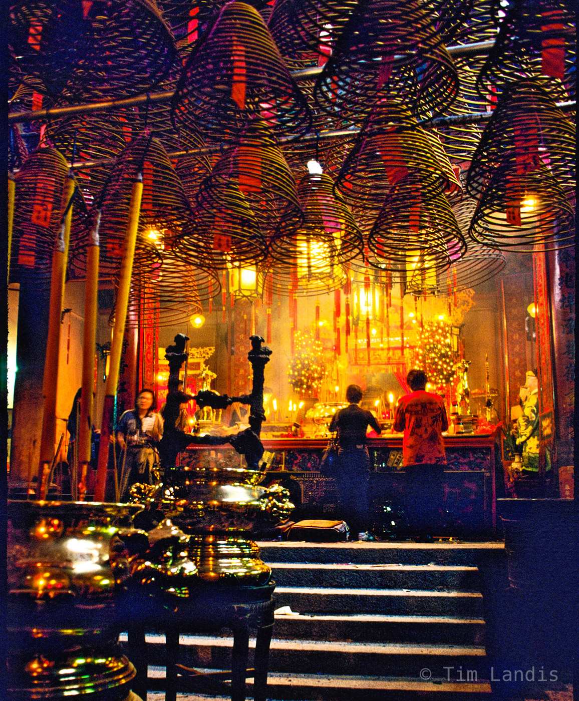 Worshippers burn incense in a smoke filled temple