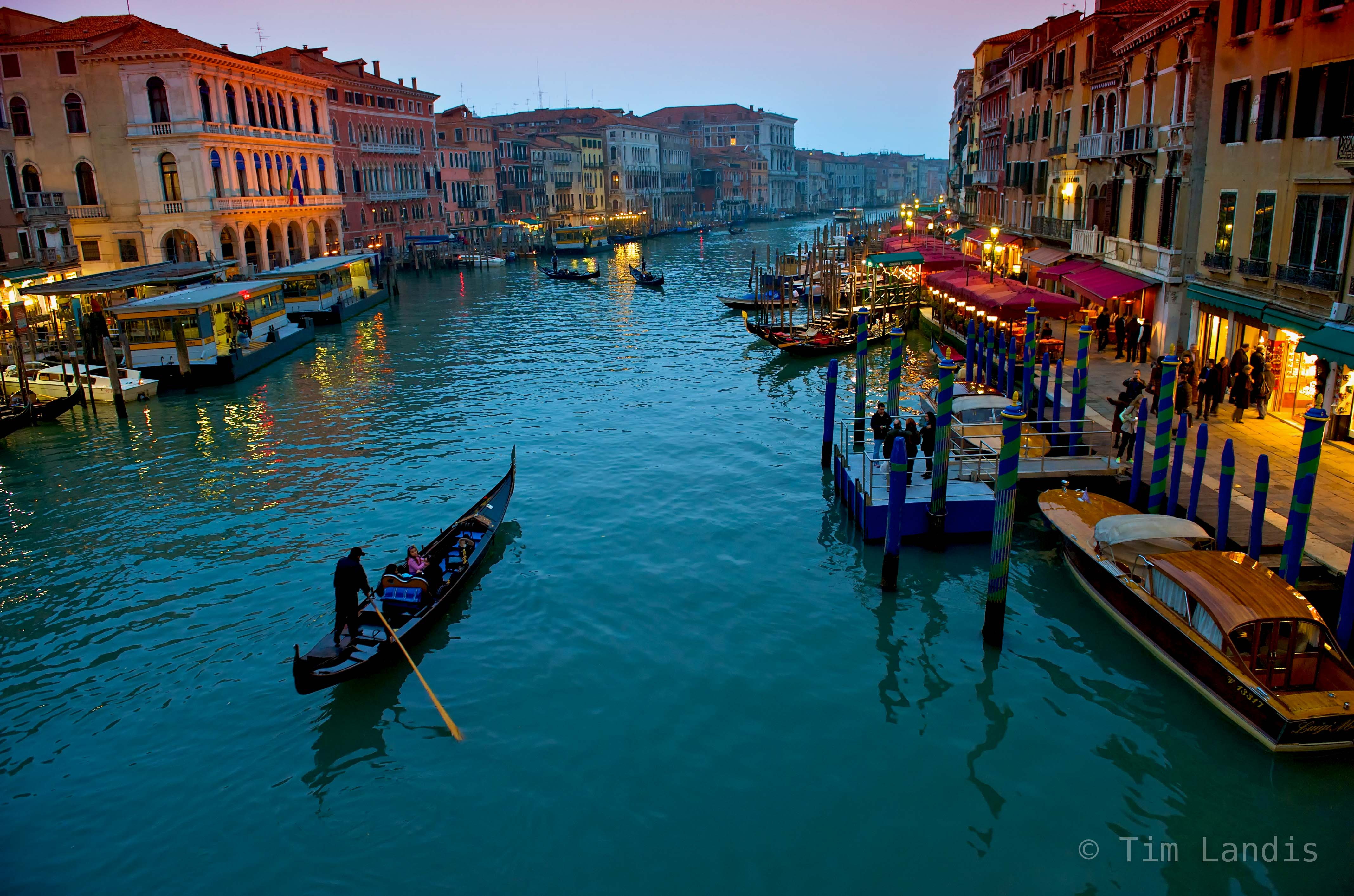 lone gondola meanders along the grand canal after sunset