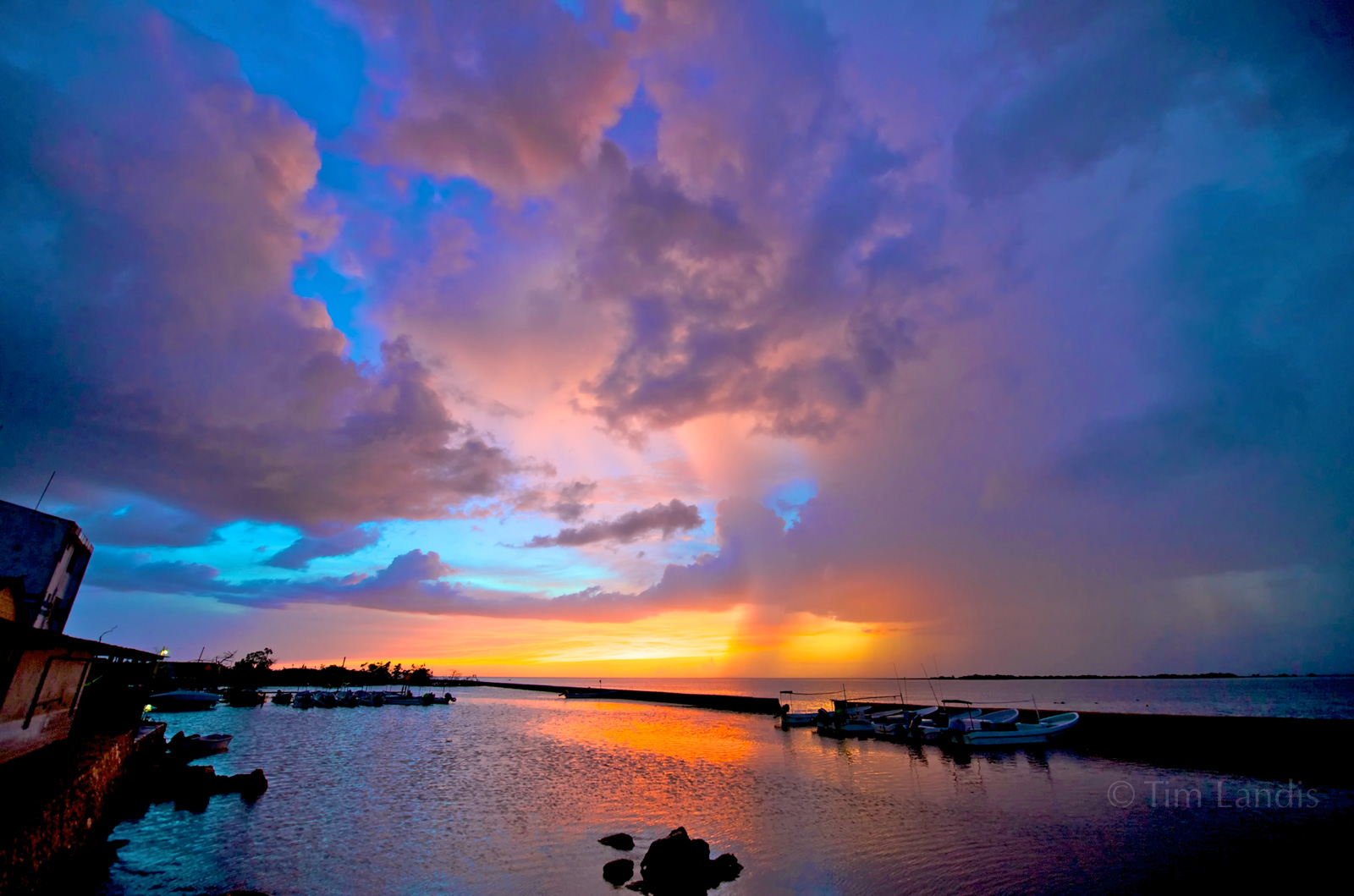 a storm approaches as the sunsets on a remote fishing village